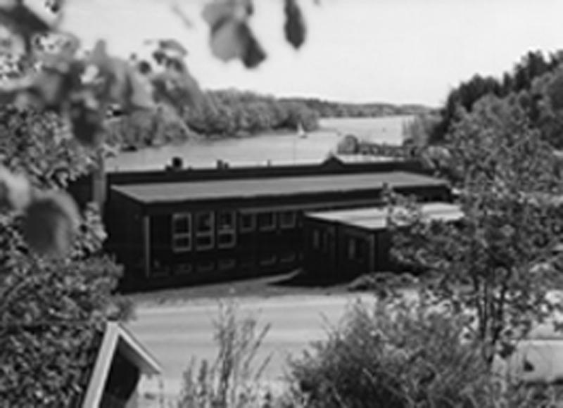 Torsten Lindholm med medarbetare flyttade från Stockholm till den lilla naturskönt belägna byn Verkebäck strax söder om Västervik. Där fanns en ledig industribyggnad vid Verkebäcks-vikens inre del. Så här såg det ut i slutet av 1980-talet.